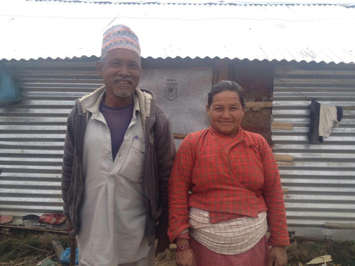 Photo of two villagers outside their tin shed