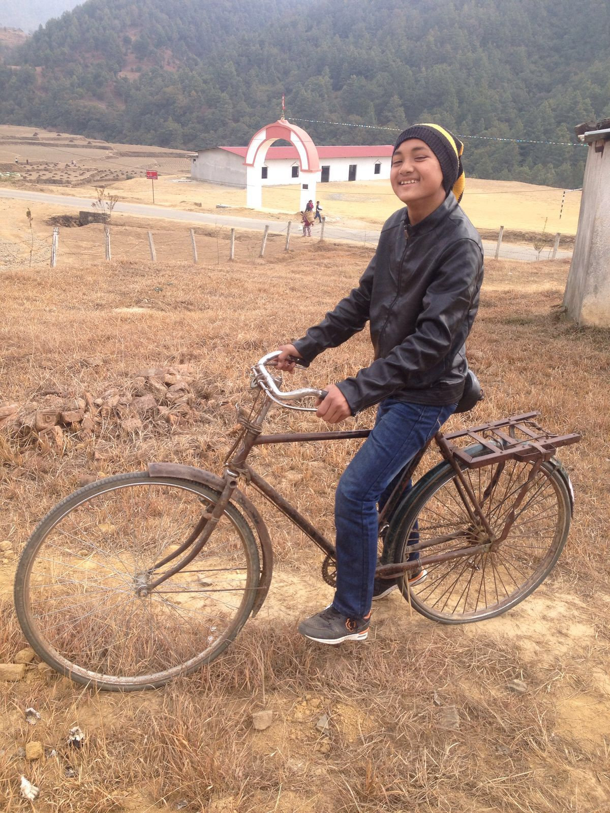 Photo of a teenage boy happily riding a rusty bicycle.