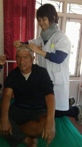 Kaikit applying scalp acupuncture on patient with post stroke sequelae